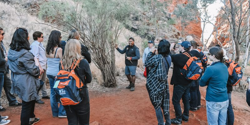 Team exploring Uluru with indigenous elder
